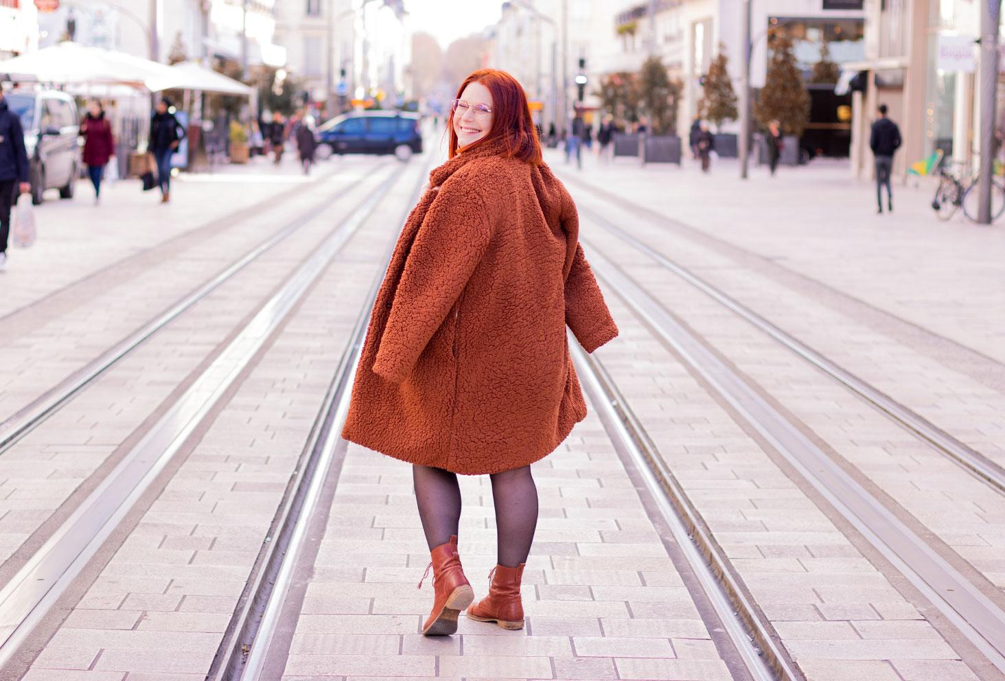 De dos au milieu de la rue Nationale à Tours, avec le manteau marron en fausse fourrure Shein sur les épaules porté en cape