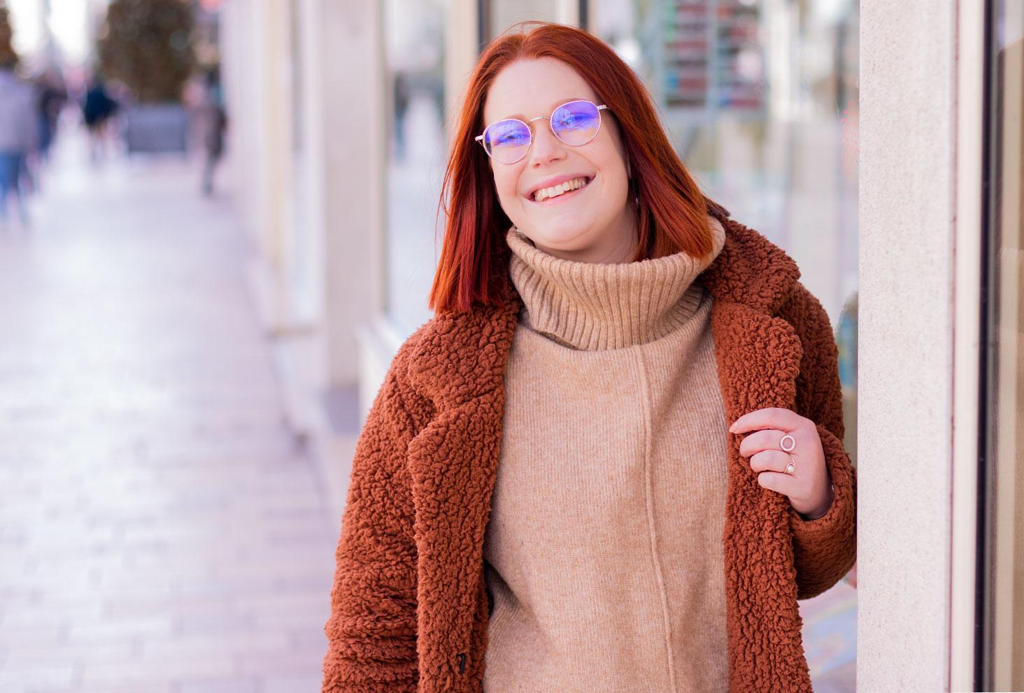 Zoom sur le manteau marron Shein en moumoute porté sur un pull à gros col roulé beige H&M, appuyé conte la vitrine d'une librairie