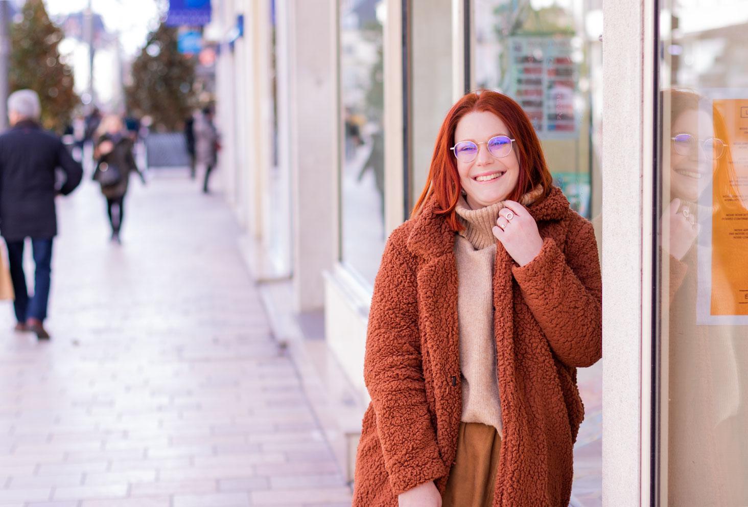 Appuyé contre la vitrine d'une grande librairie, en manteau à fausse fourrure marron Shein par dessus un pull à col roulé beige