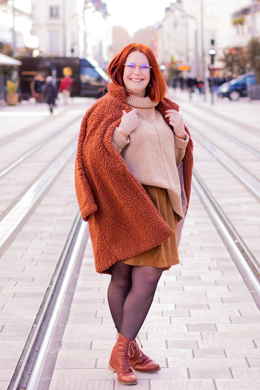 Au milieu de la rue en vêtements camaïeu de marron, un manteau sur les épaules