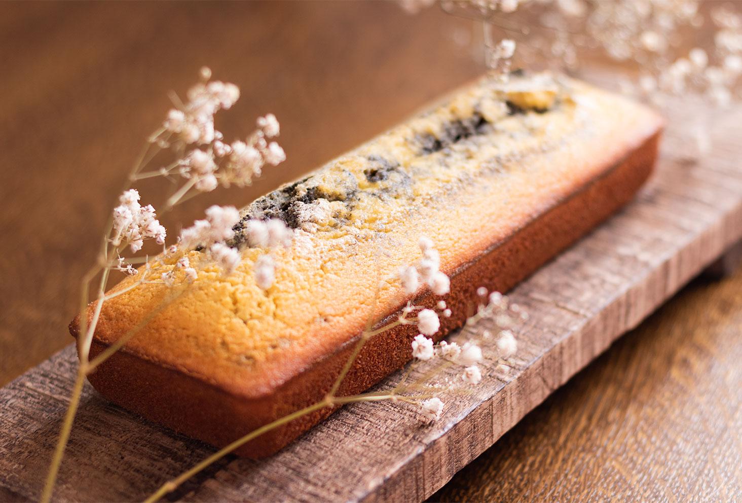Zoom sur le côté d'un marbré à la crème de sésame et à l'orange, sur une planche et une table en bois, entouré de gypsophiles blanches sèches