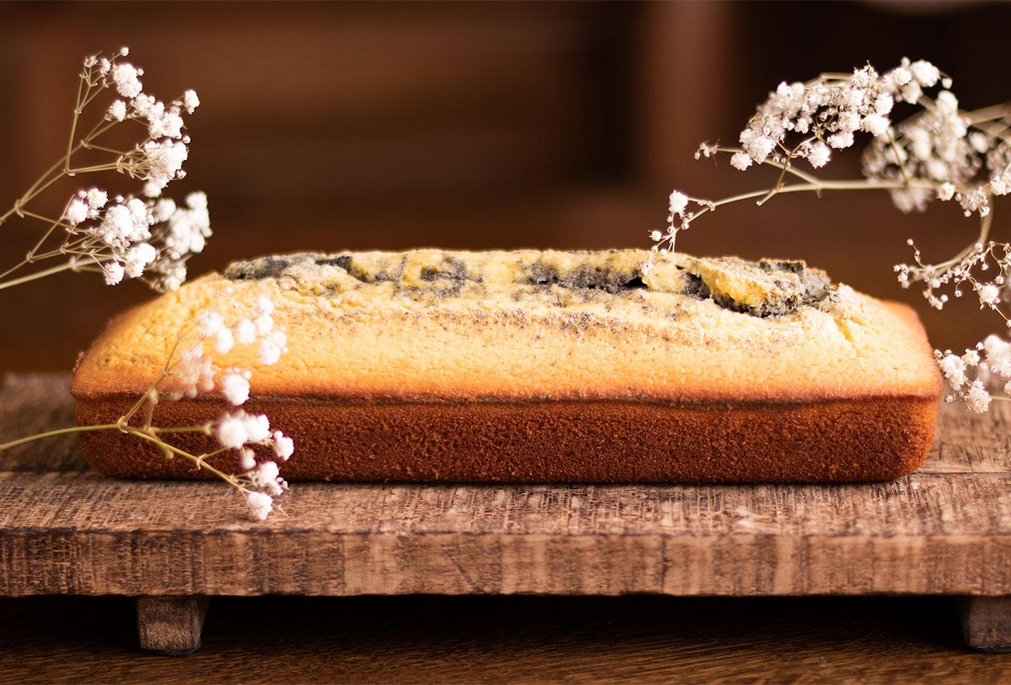Marbré à l'orange et au sésame noir posé sur une planche en bois au milieu de gypsophiles blanches