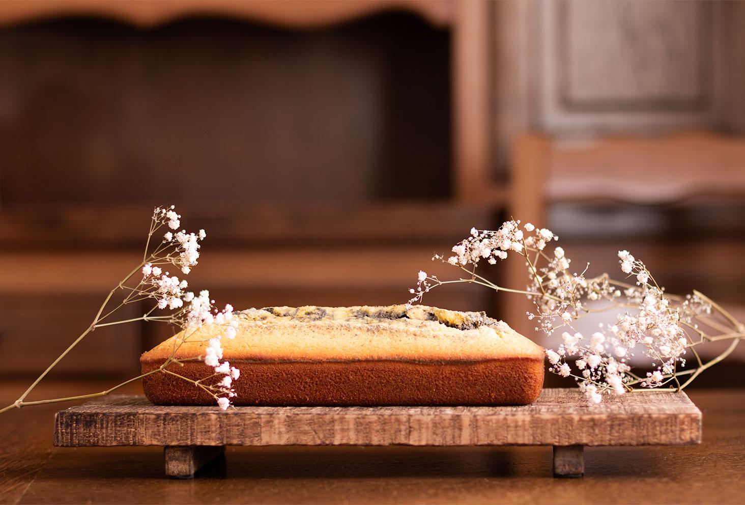 Cake marbré à l'orange et à la crème de sésame noir posé sur une planche en bois, sur une table en bois, devant un meuble en bois, au milieu de gypsophiles sèches