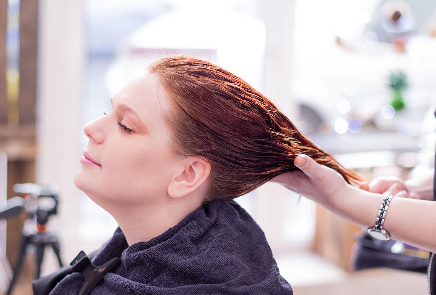 Massage crânien aux huiles essentielles au salon de coiffure Artiste en Herbes à Tours, de profil les mains de la coiffeuse dans les cheveux
