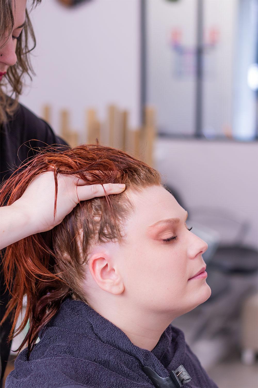 En plein massage crânien aux huiles essentielles, les mains de la coiffeuse dans les cheveux