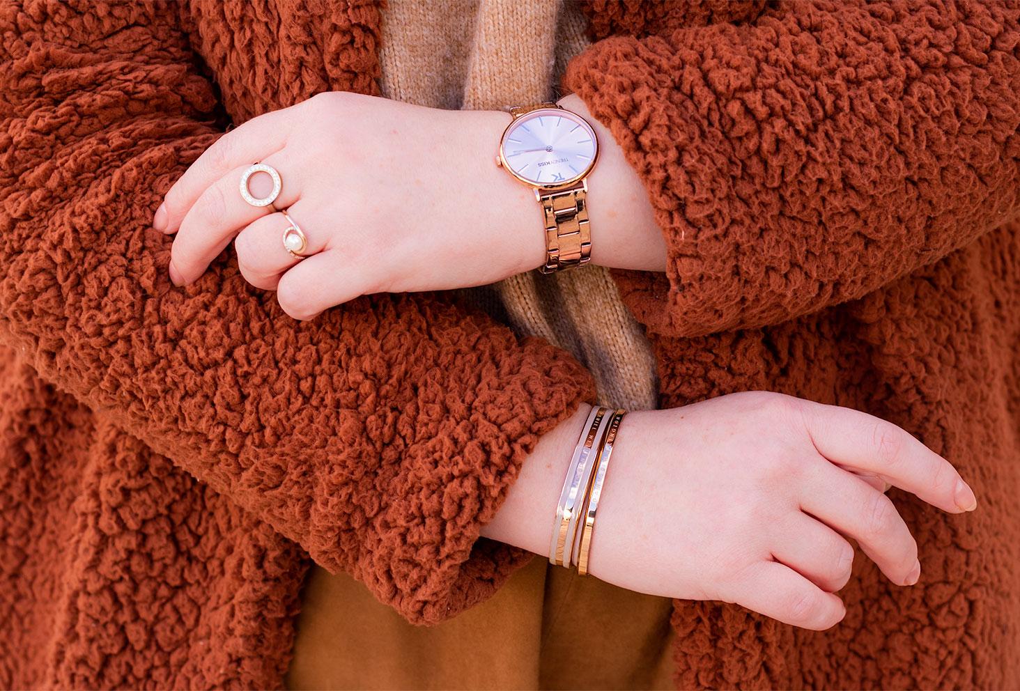 Zoom sur la montre dorée Trendy Kiss et les bracelets dorés Daniel Wellington portés avec un gros manteau moumoute marron