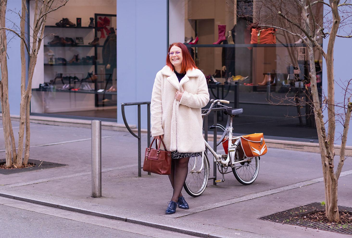 Devant la vitrine d'un magasin près d'un vélo vintage, en manteau moumoute et derbies bleues
