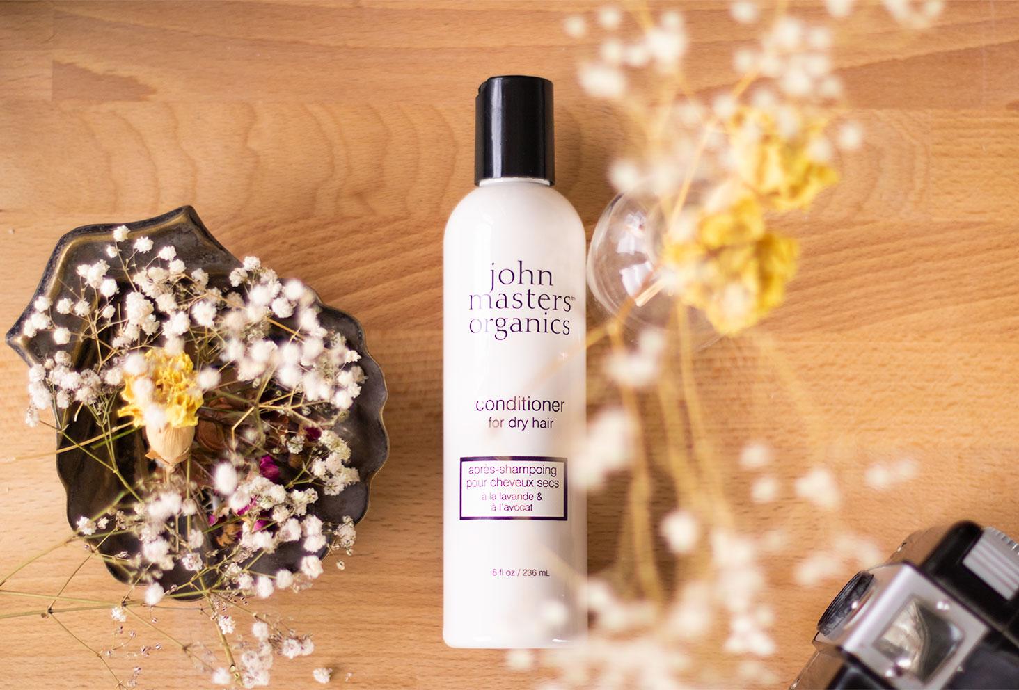 L'après-shampooing pour cheveux secs dans sa bouteille blanche et noire de John Masters Organics, posé allongé sur un bureau en bois au milieu des fleurs sèches et des objets vintages