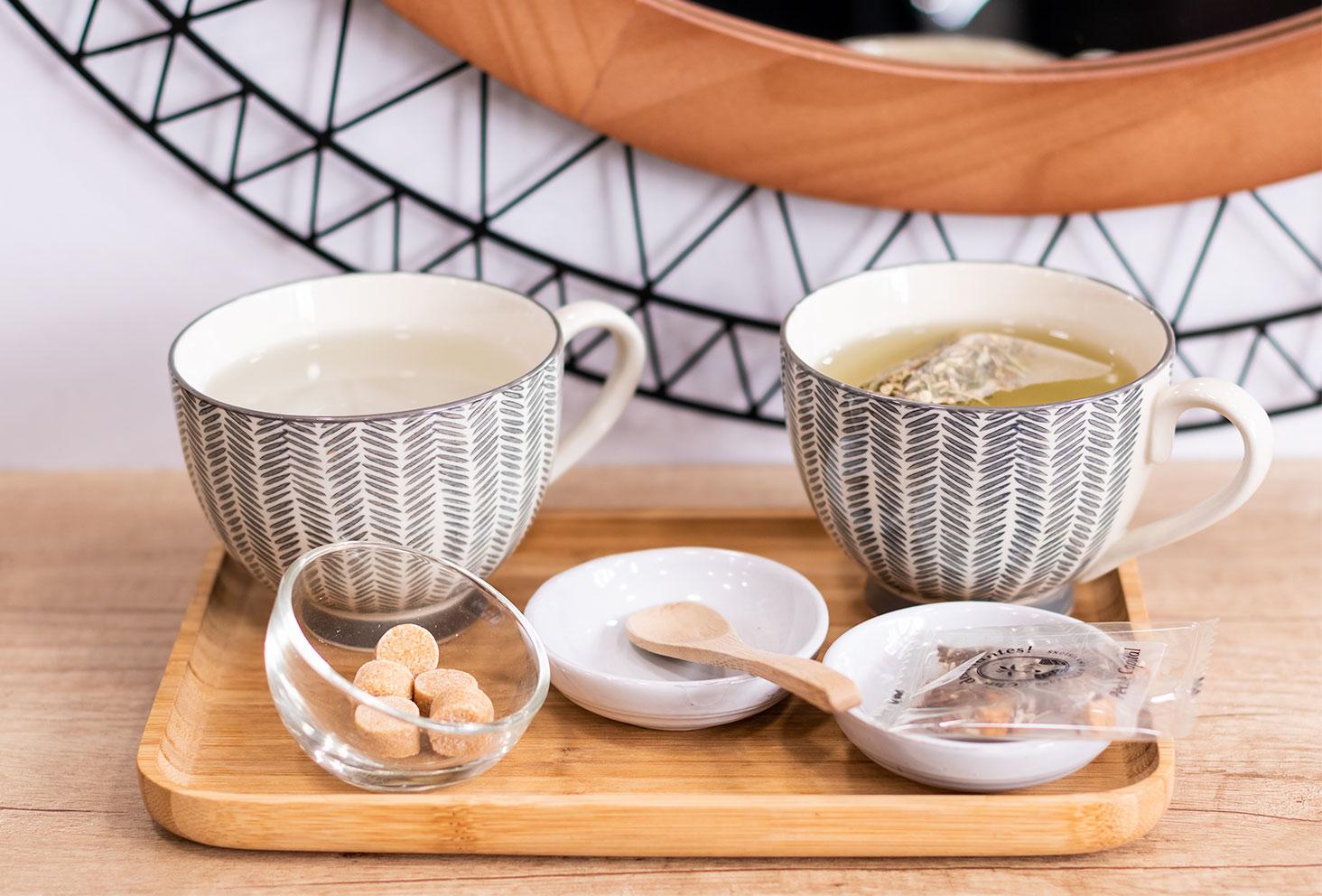 Plateau avec tasses posé sur la tablette devant le miroir, pour une pause thé avec Chic des Plantes au salon de coiffure Artiste en Herbes à Tours