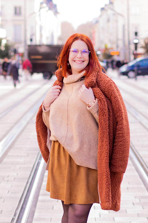 De profil en pull à col roulé et jupe en cuir camel, un manteau en fausse fourrure posé sur les épaules, au milieu de la rue