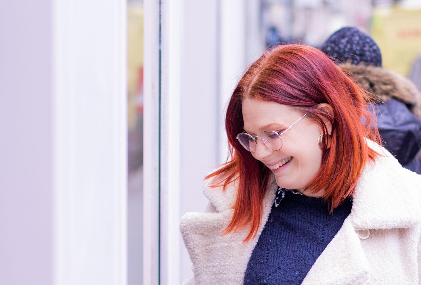 Devant la vitrine d'un magasin, de profil les cheveux derrière les oreilles, en manteau blanc épais