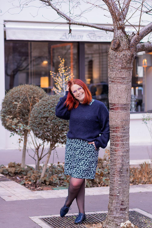 Contre un arbre la main dans les cheveux, en pull bleu par dessus une robe chemise bleue fleurie, devant la vitrine illuminée d'un magasin