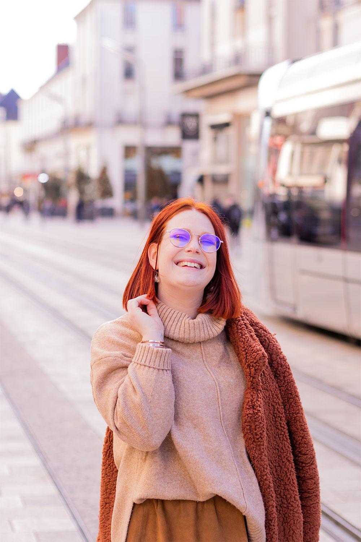 Au milieu de la rue devant le tramway de Tours, la mais dans les cheveux, en col roulé beige et manteau marron posé sur une épaule