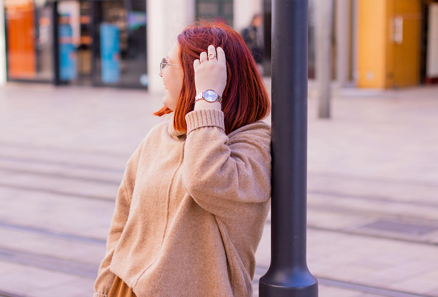 Appuyée de dos contre un poteau, au milieu de la rue, la main dans les cheveux avec la montre dorée Trendy Kiss au poignet