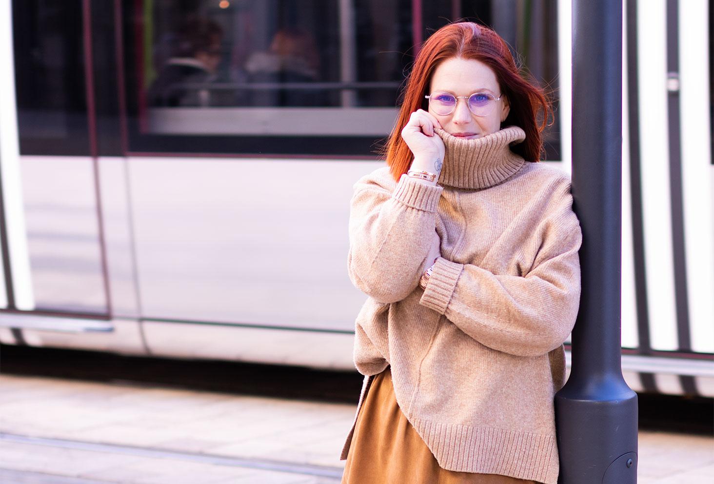 Contre un poteau devant le tramway, au milieu de la rue, le col roulé du pull remonté et les cheveux dans le vent