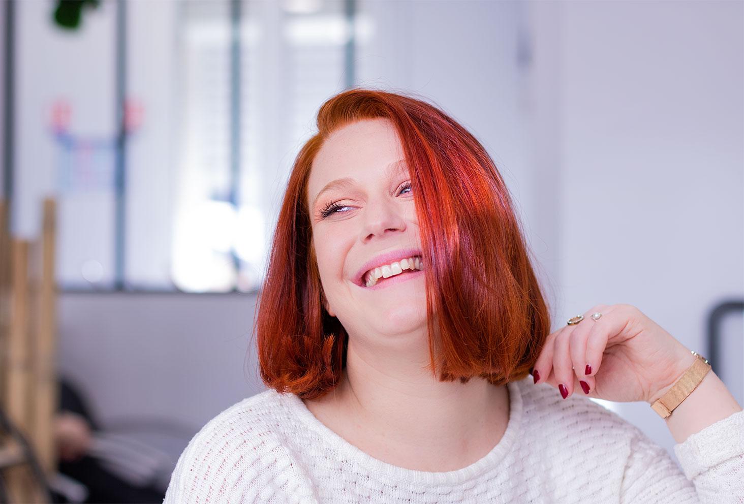 Résultat de la coloration végétale au henné naturel sur cheveux roux au salon de coiffure Artiste en Herbes à Tours, le regard de côté et la main dans les cheveux avec le sourire