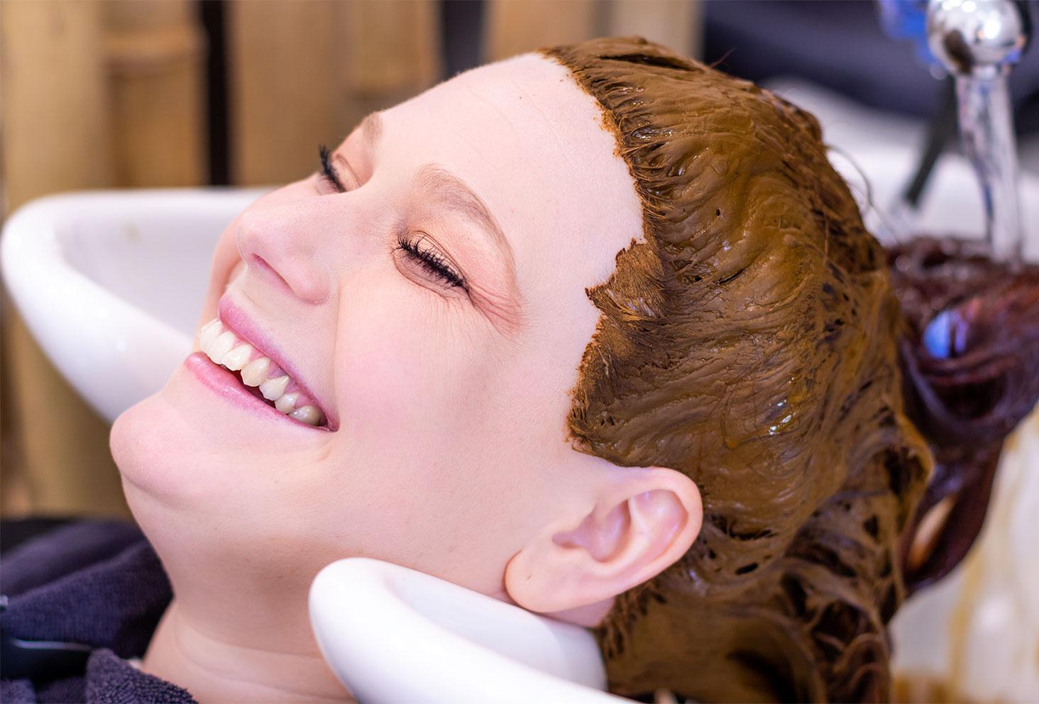 Shampoing la tête dans un bac pour rincer la coloration végétale au henné naturel dans un salon de coiffure