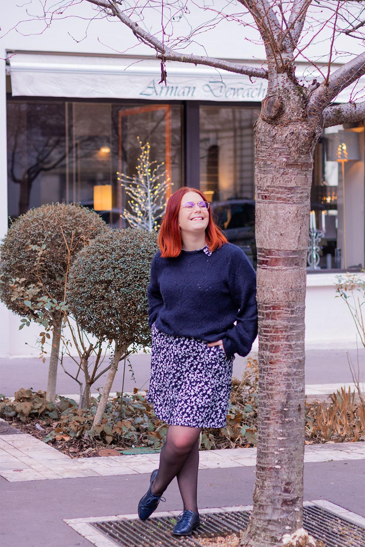 Contre un arbre les mains dans les poches, en pull bleu par dessus une robe chemise bleue fleurie et derbies vernies bleues, devant la vitrine illuminée d'un magasin