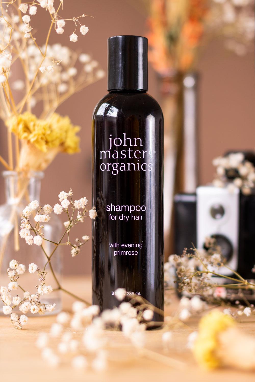 La bouteille noire du shampooing pour cheveux secs de la marque John Masters Organics posé sur un bureau au milieu de fleurs séchées et devant des vases et objets vintages