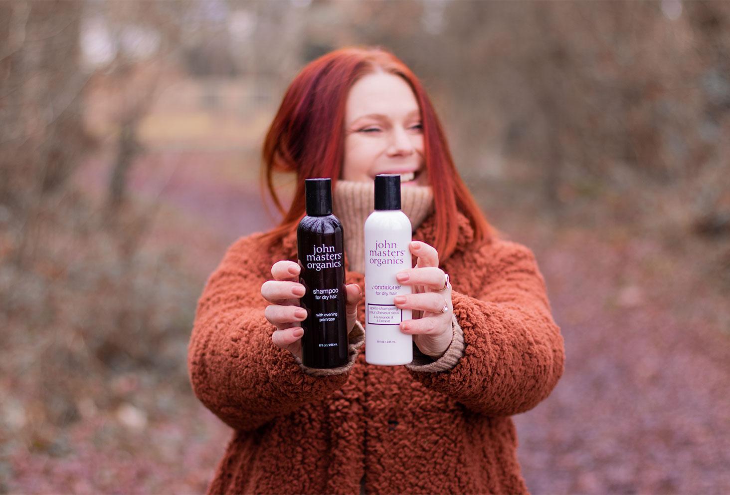 Le shampooing et l'après-shampooing pour cheveux secs de la marques John Masters Organics, tenus dans les mains bras tendu par devant, au milieu de la forêt en manteau moumoute marron