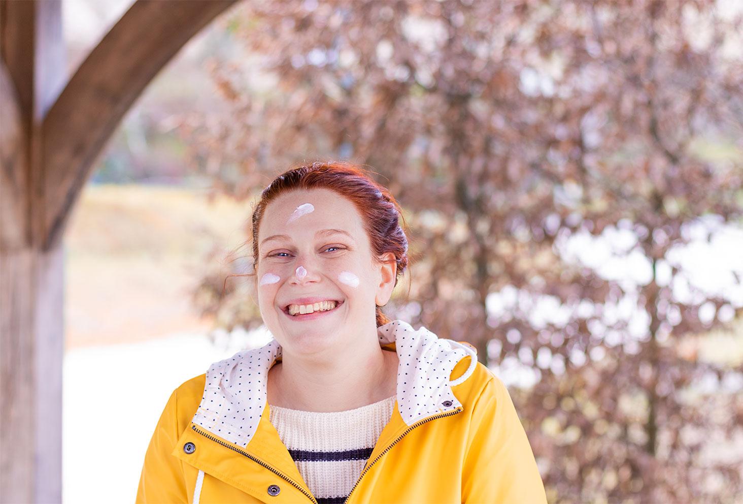 En ciré jaune, les cheveux attachés, avec de la crème hydratantes bio d'Avril sur le visage