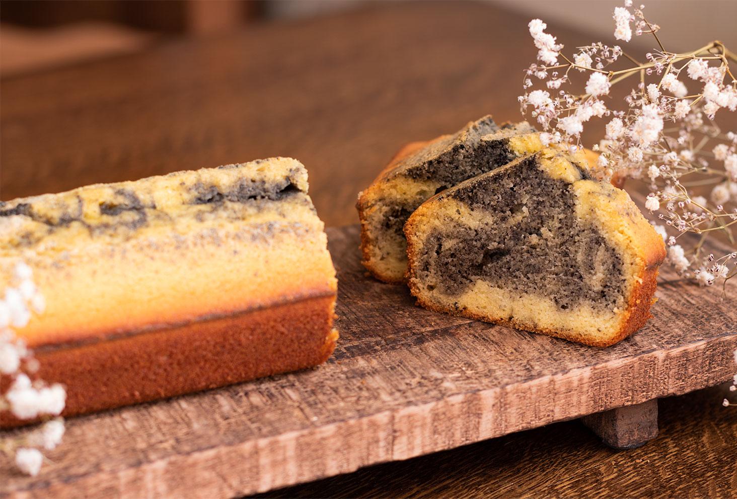 Zoom sur une part de marbré à l'orange et au sésame noir, coupée au milieu du cake sur une planche en bois