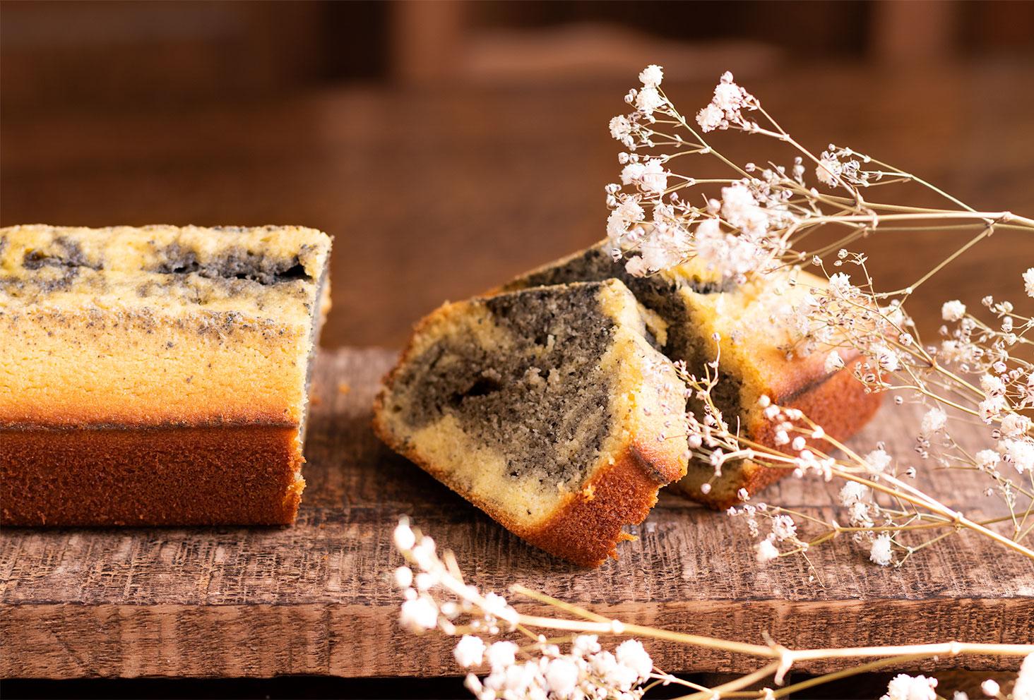 Une part de marbré à la crème de sésame noir coupée au milieu du cake, derrière un bouquet de fleurs sèches