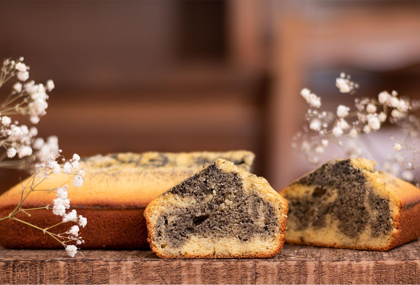 Zoom sur la texture d'un marbré orange et crème de sésame noir, posé sur une planche en bois devant le gâteau entier