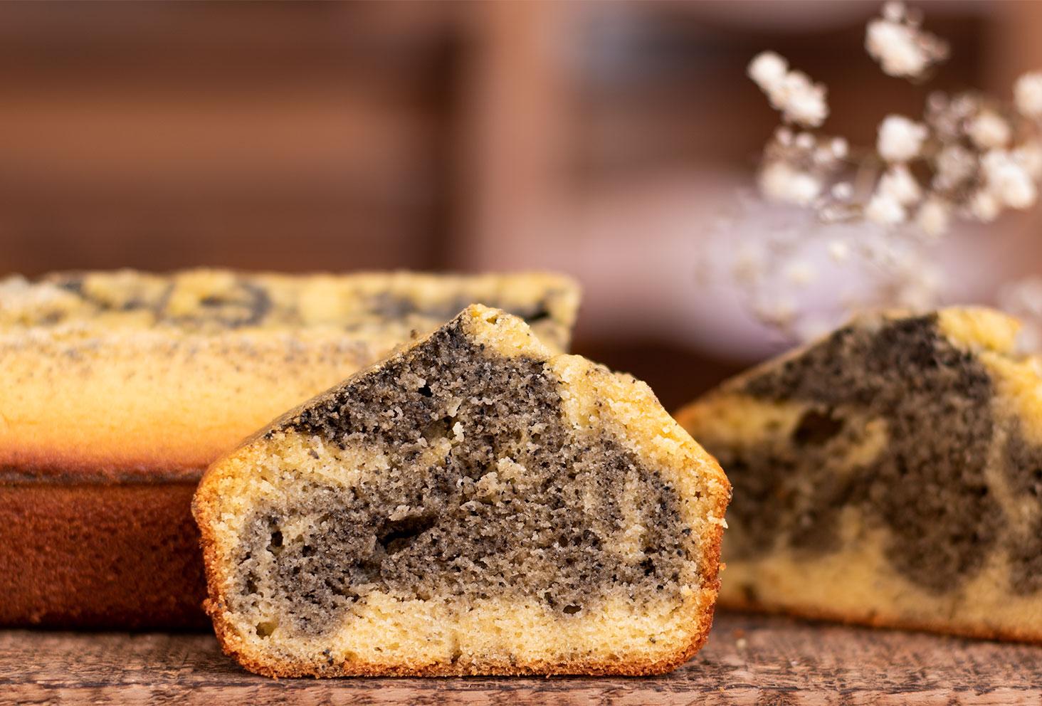 La texture d'une part de marbré à l'orange et au sésame noir, posé devant le cake marbré en entier