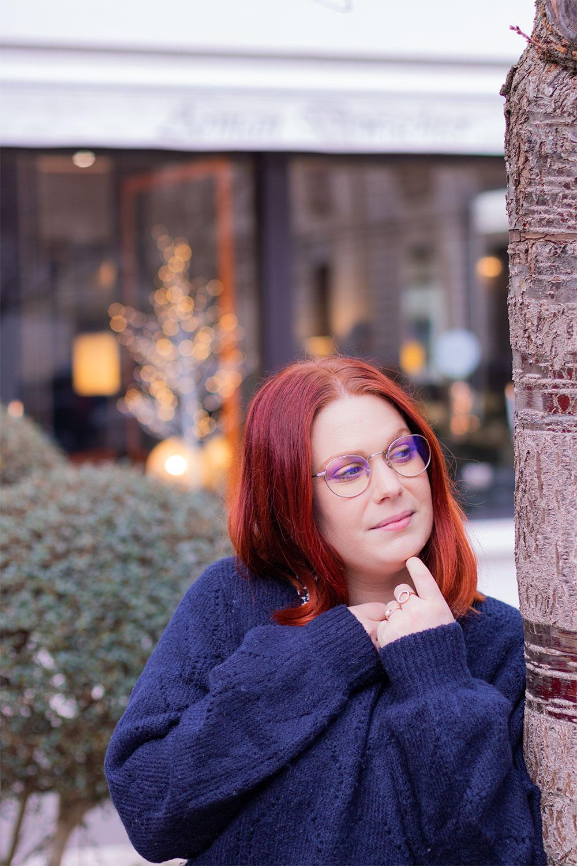 Zoom pull bleu à mailles épaisses contre un arbre, les mains sous le menton, devant une vitrine de magasin