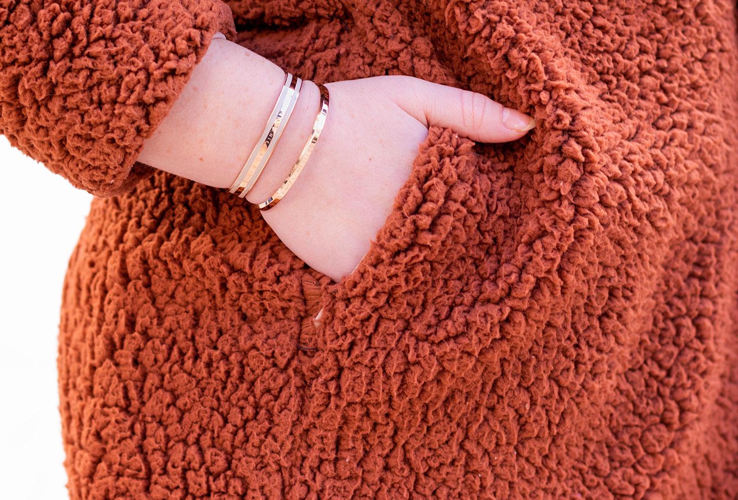 Zoom sur les bracelets dorés de Daniel Wellington portés, la main dans la poche d'un manteau en fausse fourrure marron