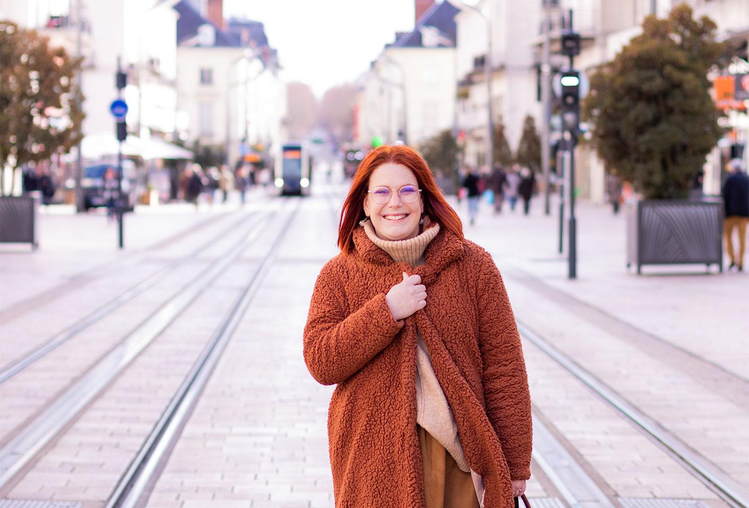 Zoom sur le manteau marron en moumoute SheIn porté par-dessus un gros pull à col roulé beige, au milieu de la rue Nationale à Tours