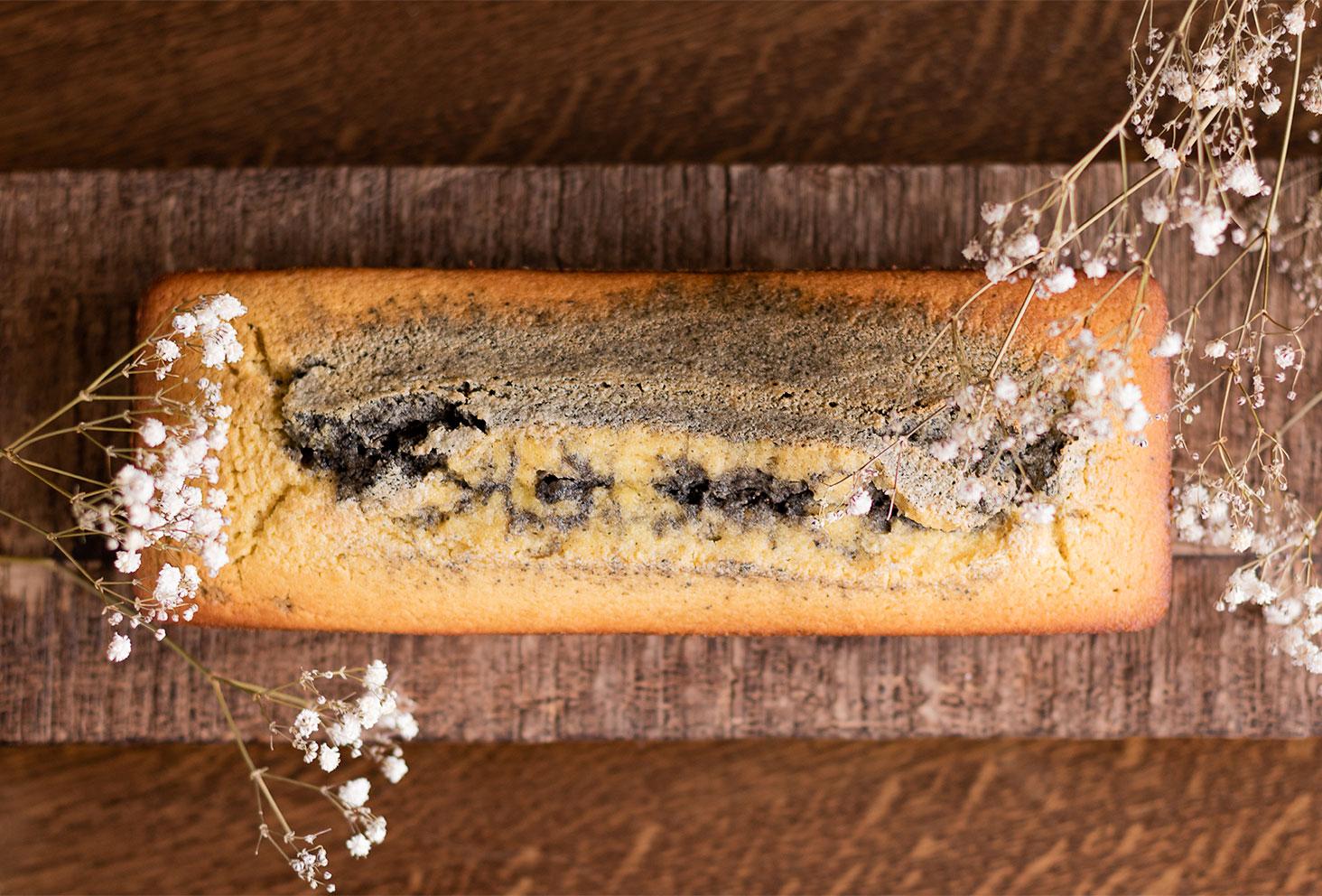 Marbré à la crème de sésame noir et à l'orange vu de haut sur une planche et une table en bois, au milieu de fleurs sèches