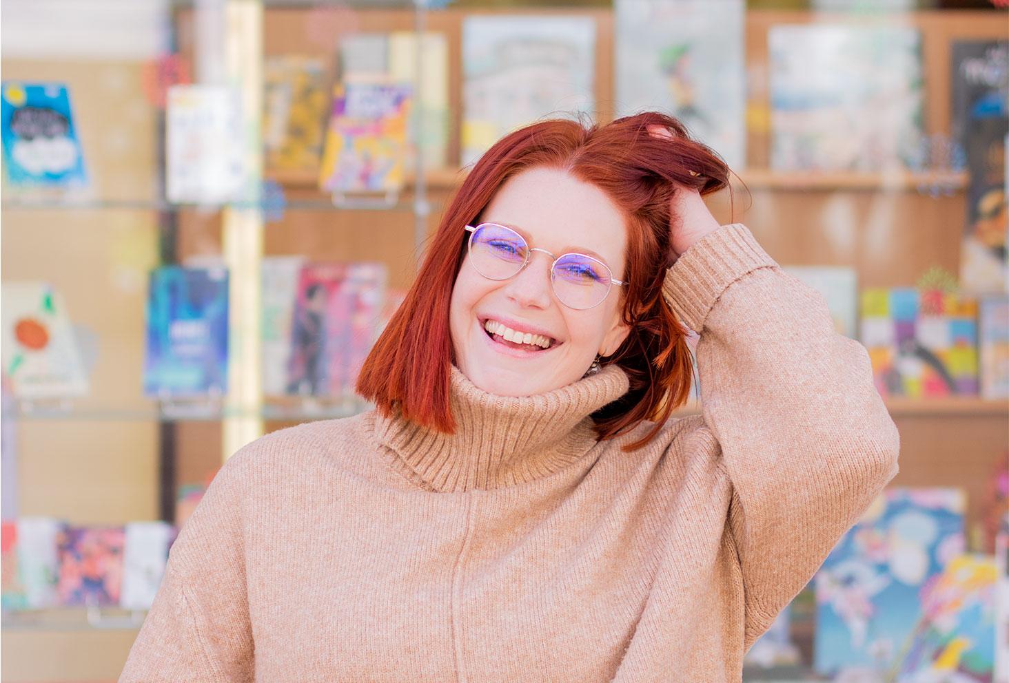 Devant une vitrine de livre avec le sourire, la main dans les cheveux, dans un gros pull à col roulé beige de la marque H&M