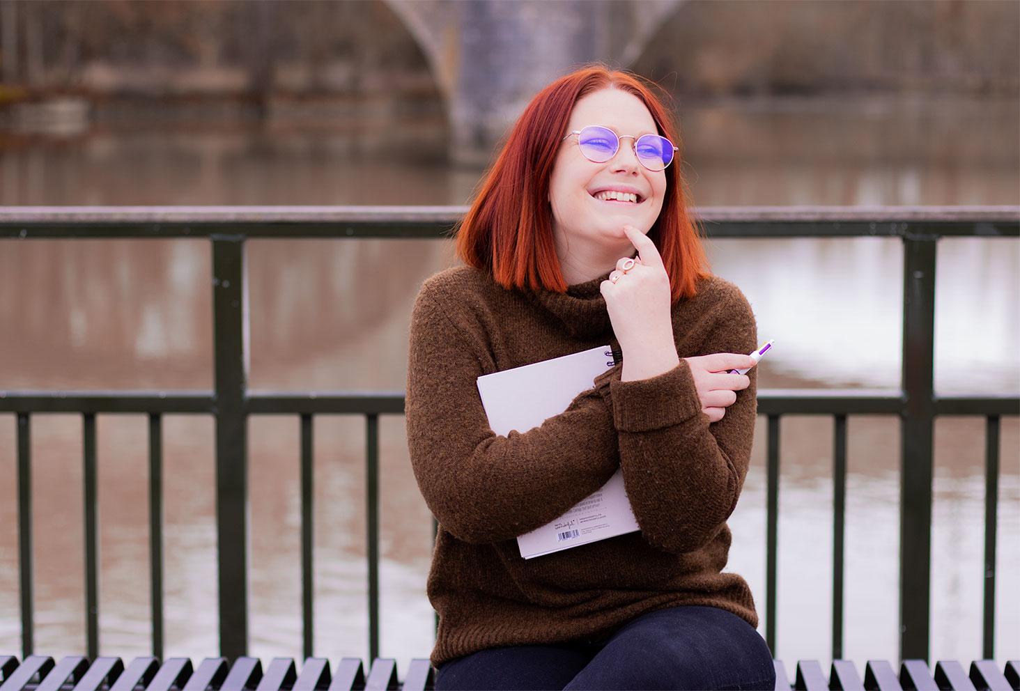 Assise sur un banc métallique face au Cher, avec un carnet entre les bras, la main sur le menton