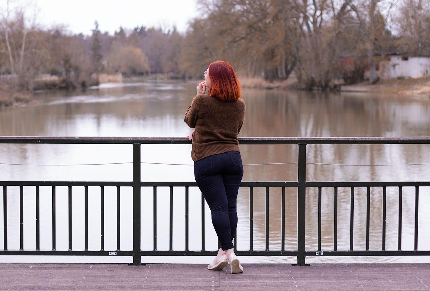 En pantalon noir et pull kaki à col roulé, de dos face au Cher, pour illustrer un article humeur concernant le doute