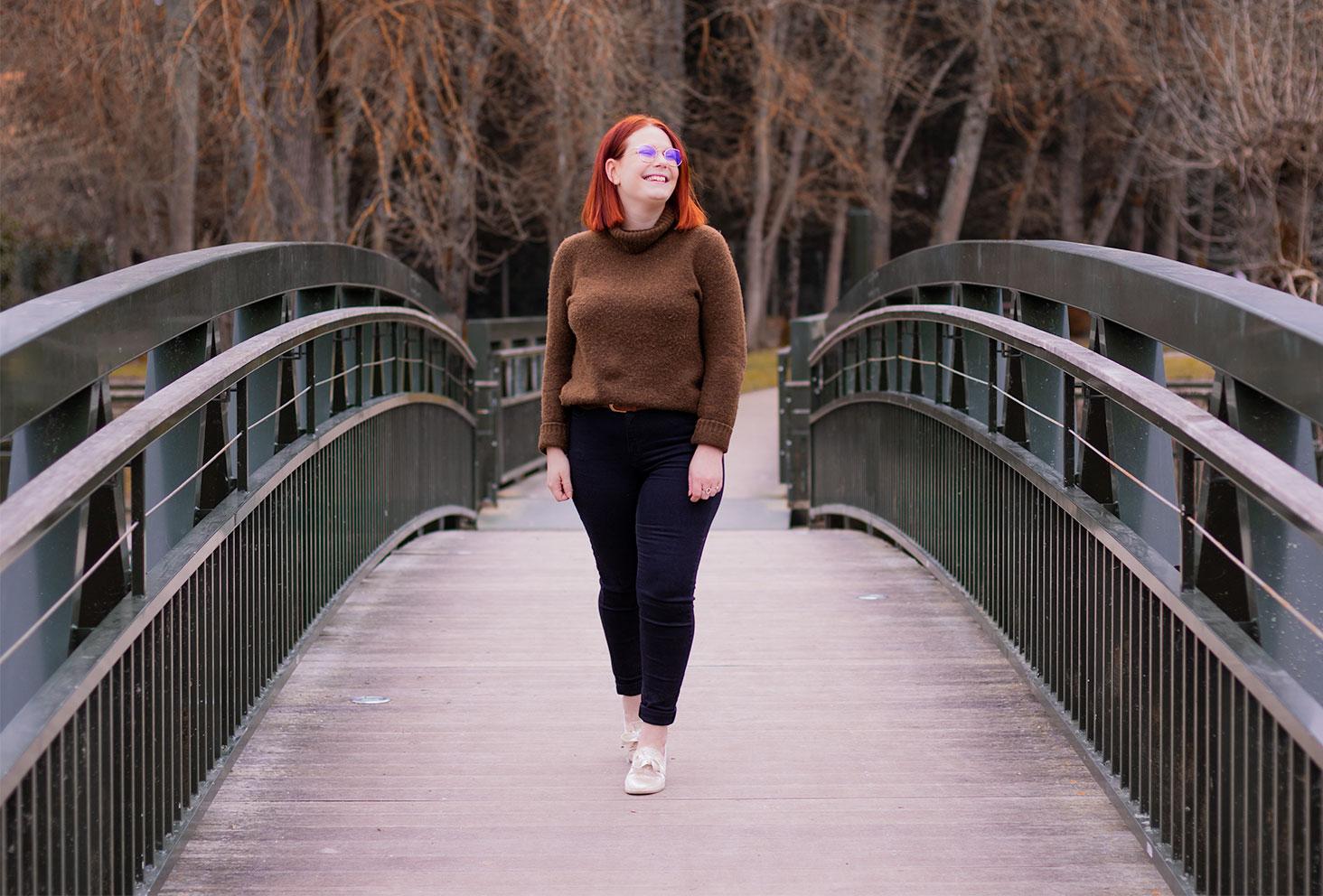 En jean noir, basket Armistice et pull kaki Camaïeu à col roulé, en train de marcher au milieu d'un pont métallique au-dessus du Cher
