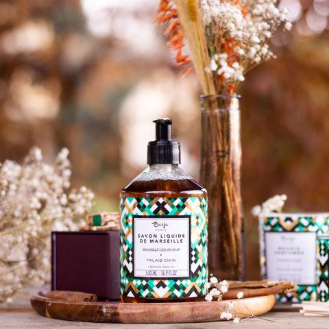 La gamme de produits pour le corps et pour la maison Palais Divin de Baïja, posée sur une table en bois au milieu de fleurs séchées avec les couleurs de l'automne en arrière plan