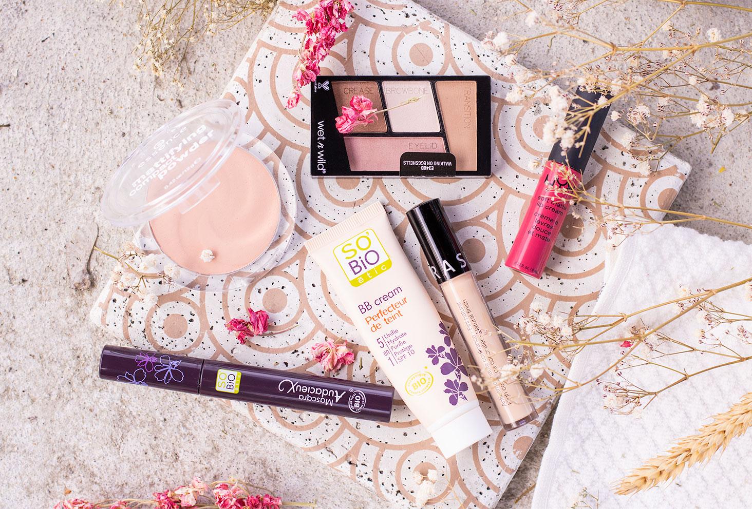 Les produits de la trousse à maquillage à moins de 50€ posé sur une dalle en béton au milieu des fleurs séchées