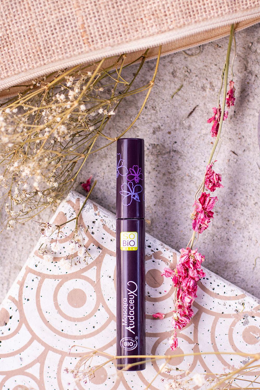 Le mascara Audacieux de SO'BiO étic posé sur une dalle en béton à motifs dorés, à côté d'une trousse de maquillage en paille pleine de fleurs séchées roses et blanches