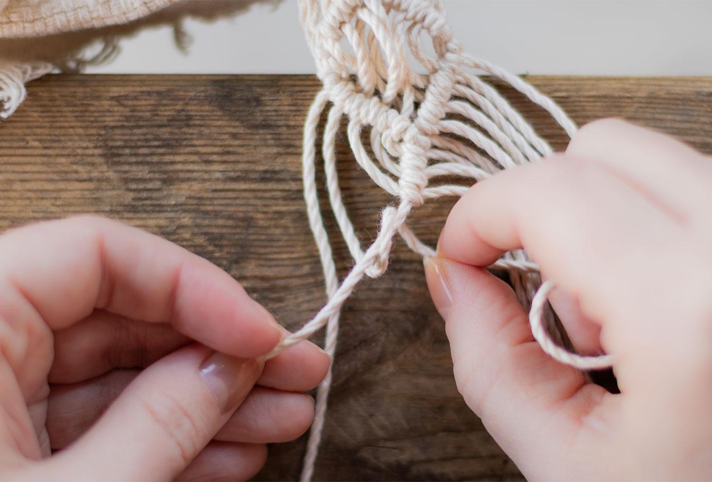 Zoom sur l'étape 3 d'un nœud de feston,posé sur une table en bois