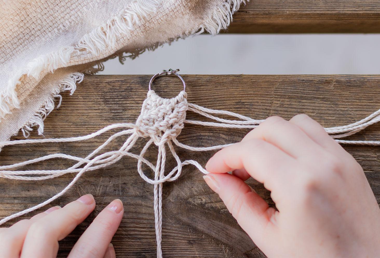 Réalisation d'un nœud demi-plat pour macramé posé sur une table en bois