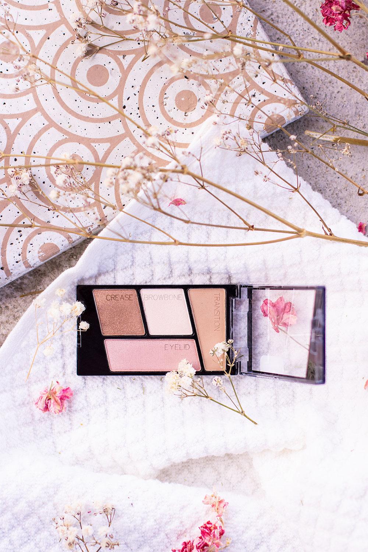 La palette nude de Wet'n'wild posé sur une serviette blanche au milieu de fleurs séchées, à côté d'une dalle en béton dorée