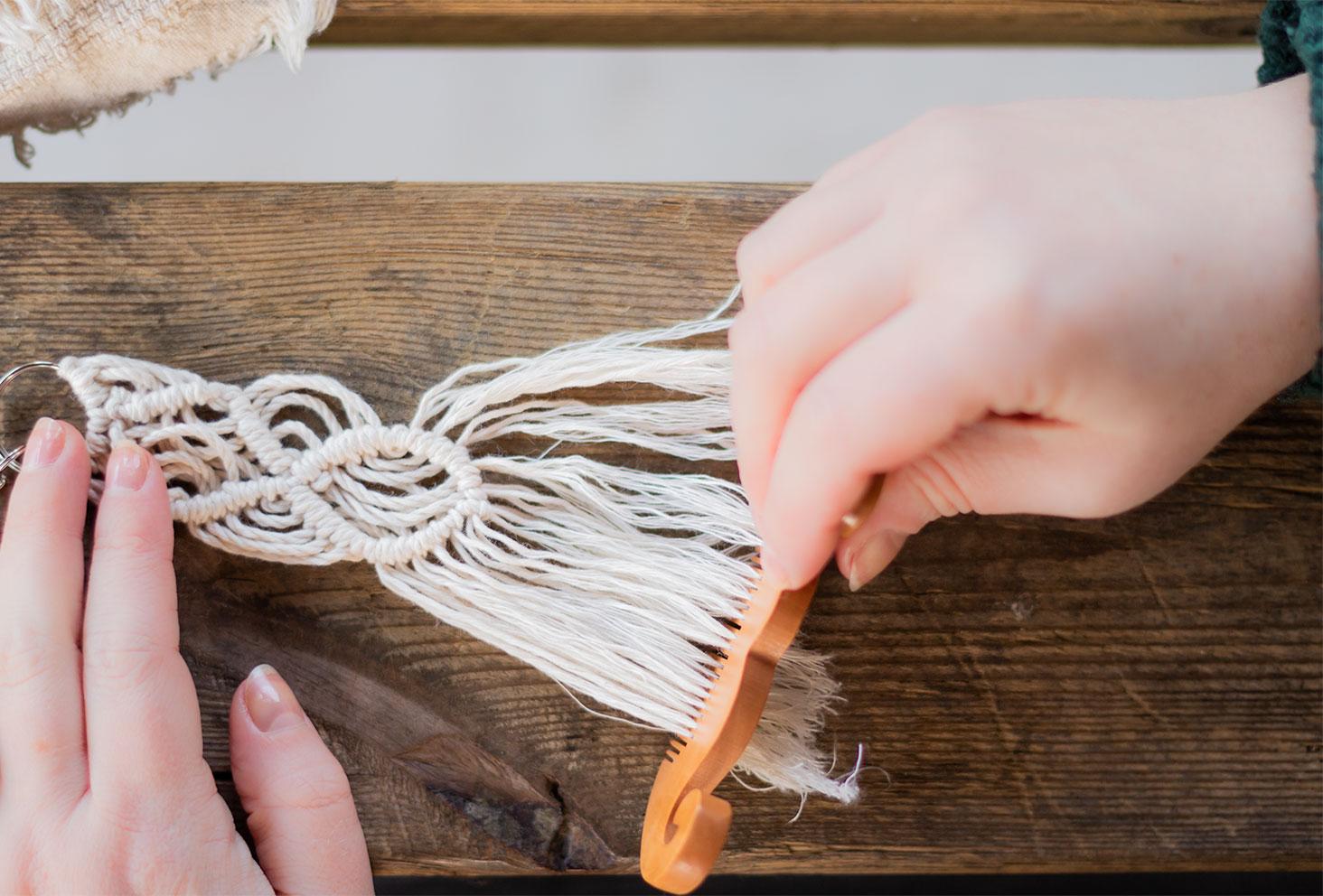 Zoom sur le brossage des brins de macramé pour e terminer, sur une table en bois à l'aide d'un peigne