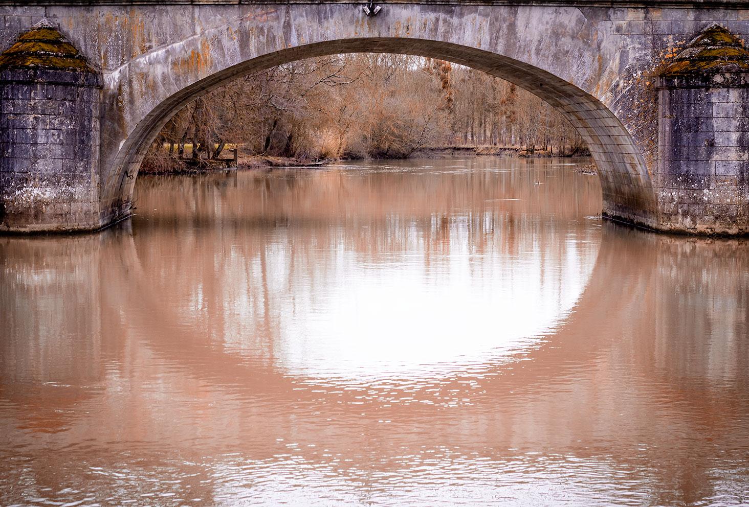 Photo paysage d'un pont en pierre au-dessus du Cher aux couleurs de l'automne-hiver