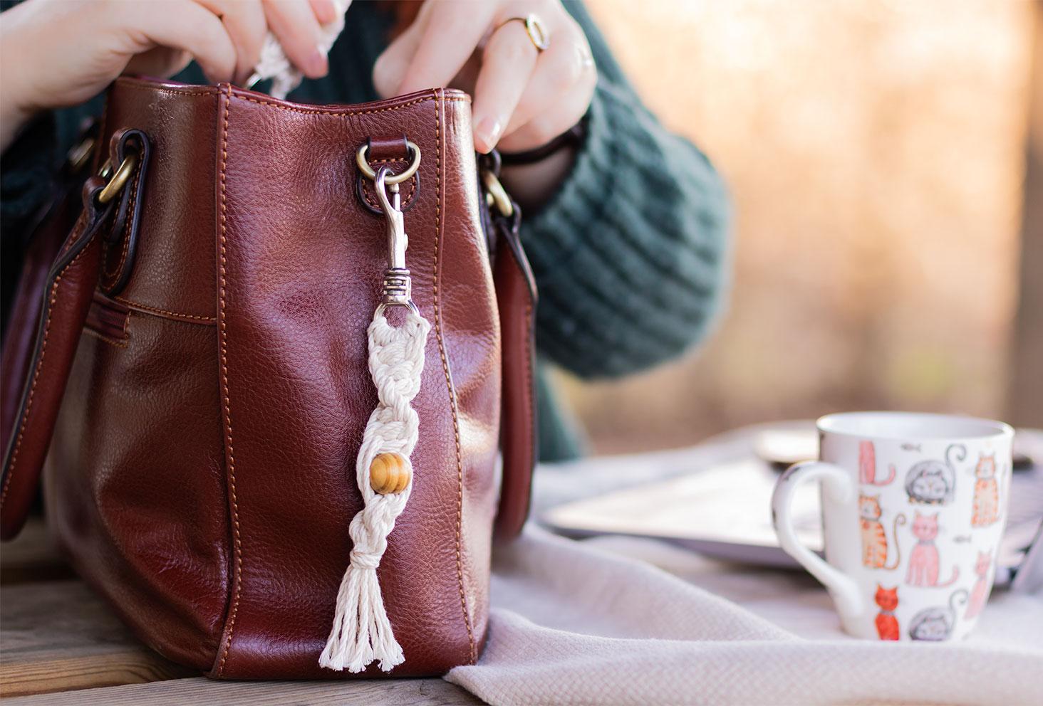 Zoom sur le porte-clés macramé en grosse torsade à 12 brins, accroché sur le côté du sac à mains