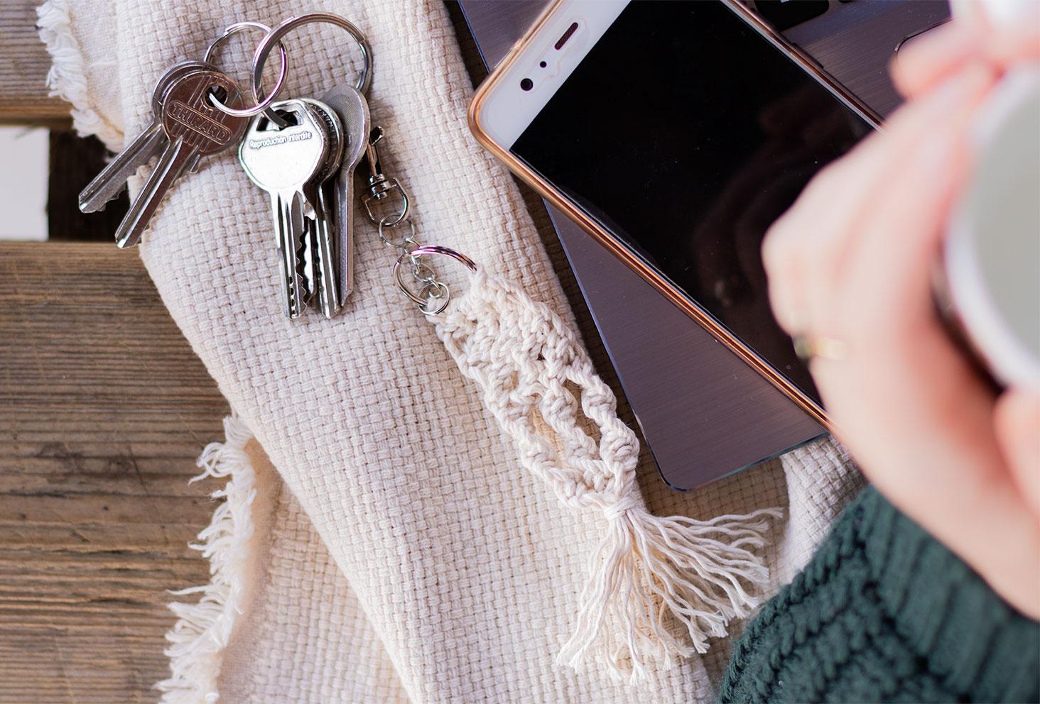 Zoom de haut sur le porte-clés macramé, accroché aux clés posé sur un plaid à côté d'un téléphone portable