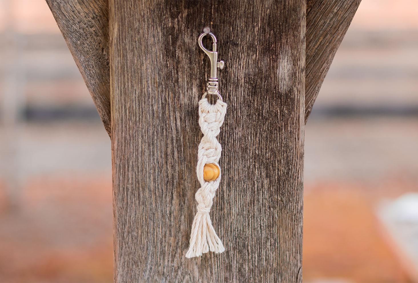 Le porte-clés macramé torsadé, accroché à une pointe sur un poteau en bois