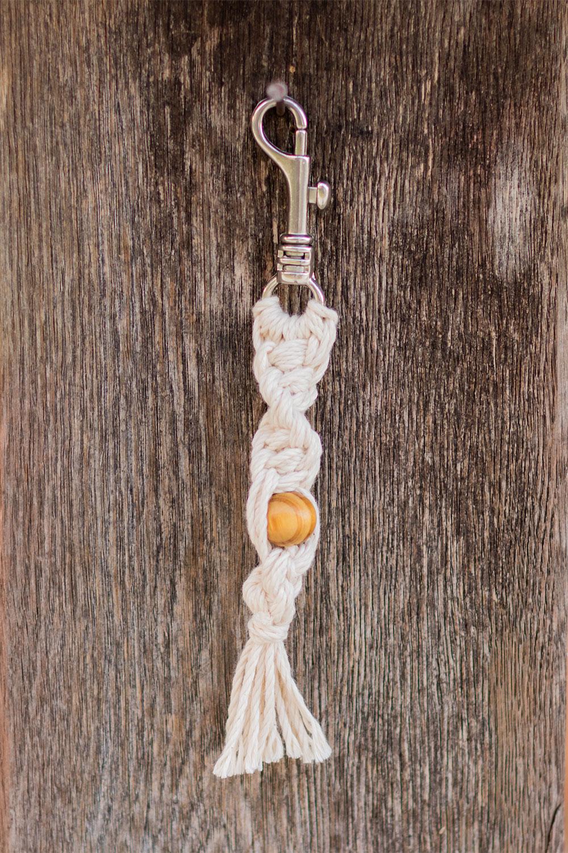 Porte-clés macramé torsadé à perle, accroché à un poteau en bois