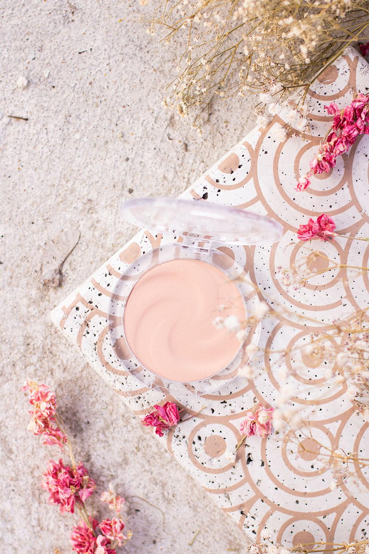 La poudre compacte matifante d'Essence, vue de haut, posé sur une dalle en béton aux motifs dorés, au milieu des fleurs roses séchées